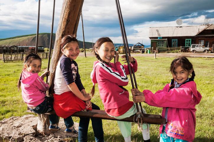 Jakutische Mädchen spielen vor einem Bauernhaus