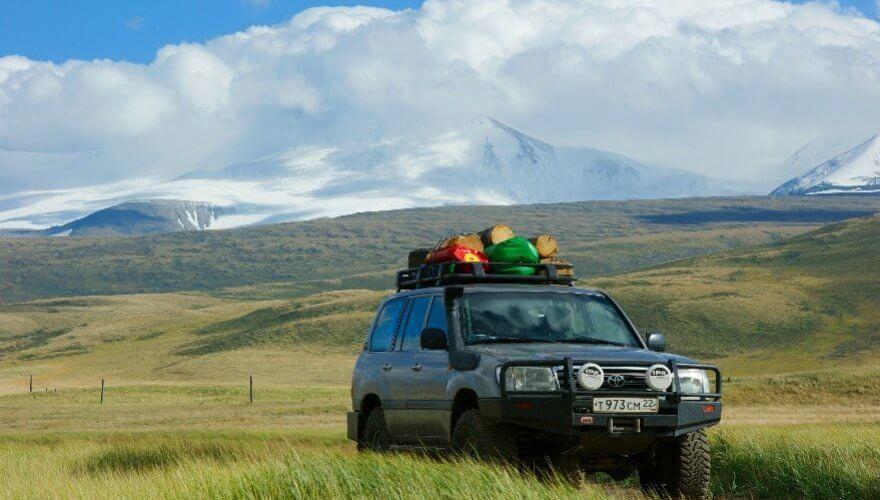 Beladener Geländewagen vor Bergen