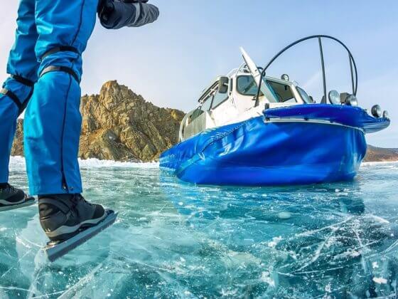 Luftkissenboot und Eisskater auf zugefrorenem Baikalsee